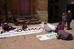 Activistas de podemos pintando una pancarta en Oviedo
